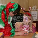 A small girl enjoying our Craft Workshop whilst being shown what do do by one of Santa's elves.