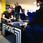 Onlookers watch as employees on their lunch break take part in the Atari Pong Table Hire