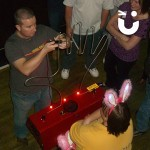 A group of spectators watch a man attempt the Hand Buzz wire Hire