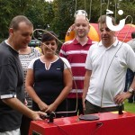 A gorup of guest spectate a contestant on the Hand Buzz wire Hire during a fun day event
