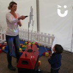 A child watches in amazement as a women guides the wand through the Hand Buzz wire Hire