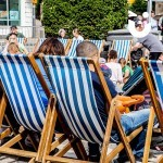 People enjoying a relaxing sit down on our blue and white Deckchair Hire