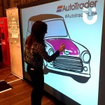 The Digital Graffiti Wall being used by an guest for an Auto Trafer Exhibition, where a mini is being painted on the digital screen