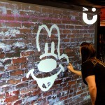 A guest at an event is using the infrared spray cans to paint a smiley face on a virtual wall on the Digital Graffiti Wall