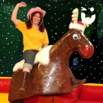 women in pink hat and yellow hat sat on the Rodeo Reindeer Hire