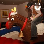 Man fully dressed as a cowboy sat on the Rodeo Reindeer Hire