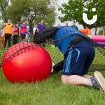 man with space hopper going under the scramble net