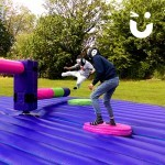 Two guests of a family fun day take on the sweeper arm of the Wipeout Challenge which they have to jump over and duck under