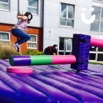 A guest at a University Event takes of 3 others in the wipeout, which sweepers arms spin around trying to take out the challengers