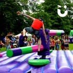 At a community fun day event, guests watch on as users of the wipeout challenge try to avoid the sweeper arms taking them out of the game.