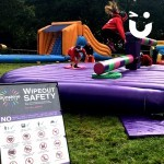 Guests of an outdoor family fun day take on the challenge of the wipeout. A young girl jumps over the sweeper arm as the next competitor steadies them self ready.