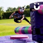 A child at a family fun day event taking on the challenge of the Wipeout Inflatable Challenge Hire, jumping over the sweeper arm as it spins round