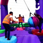 Guests enjoying the inflatable wrecking ball at a company fun day event for staff