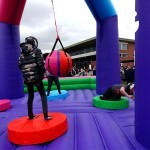 Children using the Wrecking Ball Inflatable on hire from Sunshine Events at a community Fun Day