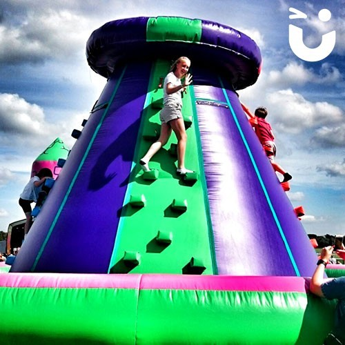 A girl waving whilst at the top of the Climbing Wall Inflatable