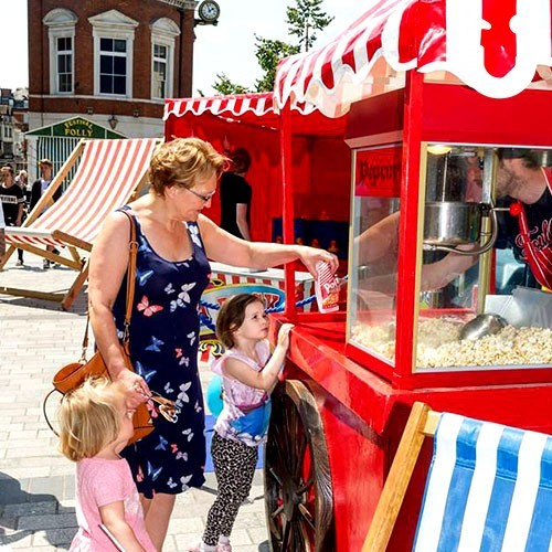 Children waiting with their mum as they get the Popcorn Fun Foods Hire