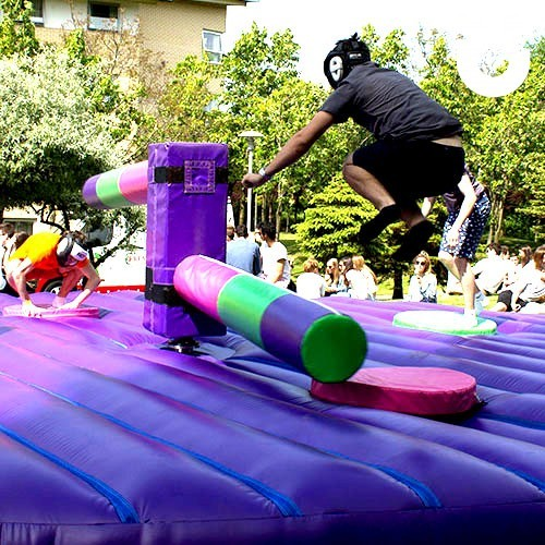 Guest at a corporate family fun day jumping over the sweeper arm of the inflatable wipeout challenge, on hire from Sunshine Events
